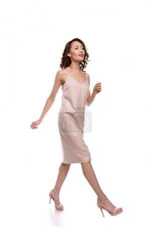 Photo for Gorgeous young asian woman in pink dress walking and looking away isolated on white - Royalty Free Image