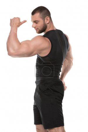 Photo for Side view of young muscular man showing biceps isolated on white - Royalty Free Image