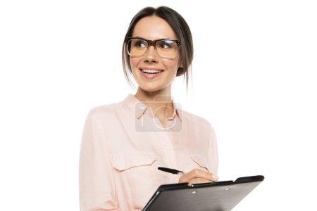 Photo pour Souriant jeune femme d'affaires écrivant sur presse-papiers et regardant loin isolé sur blanc - image libre de droit