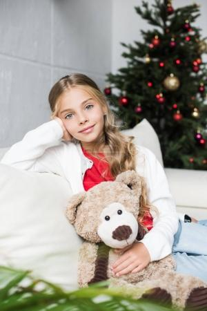 child with teddy bear at christmas tree
