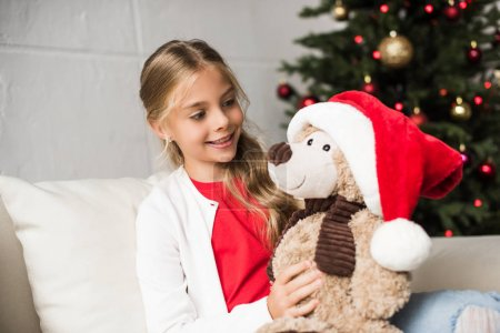 child with teddy bear at christmastime