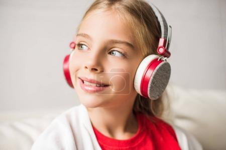child listening music with headphones