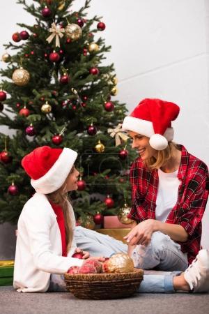 Photo pour Mère et fille en chapeaux santa souriant mutuellement tout en décorant le sapin de Noël - image libre de droit
