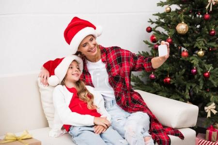 Photo for Beautiful smiling mother and daughter in santa hats taking selfie with smartphone - Royalty Free Image