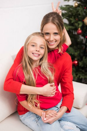 mother and daughter embracing at christmas tree