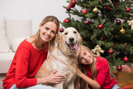 mother and daughter embracing dog