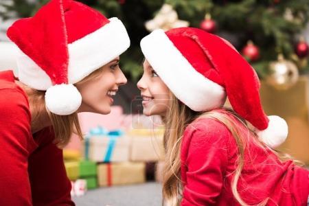 Photo pour Excité mère et fille dans chapeaux de Père Noël en se regardant - image libre de droit