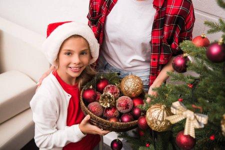 Photo pour Photo recadrée de mère et la fille tenant des bulles tout en décorant le sapin de Noël - image libre de droit