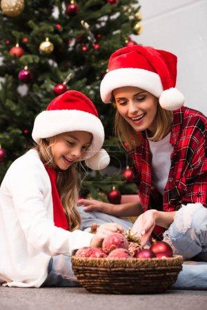 Photo pour Joyeuse mère et fille en chapeaux santa boules brillantes en regardant tout en décorant le sapin de Noël - image libre de droit