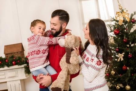 Photo pour Heureux père portant mignonne petite fille et mère souriante tenant ours en peluche à Noël - image libre de droit