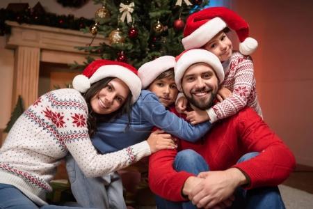 Photo pour Portrait de la famille heureuse chapeaux santa étreignant et souriant à la caméra - image libre de droit