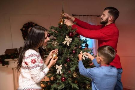 Photo pour Famille décoration arbre de Noël ensemble à la maison - image libre de droit