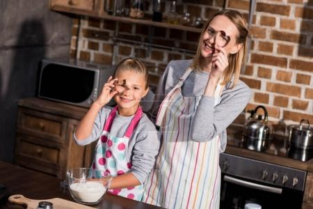 Photo for Portrait of smiling family in aprons looking at camera through cookie cutters in hands - Royalty Free Image