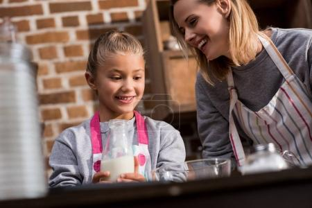 Photo for Mother and preteen daughter in aprons making cookies together at home - Royalty Free Image