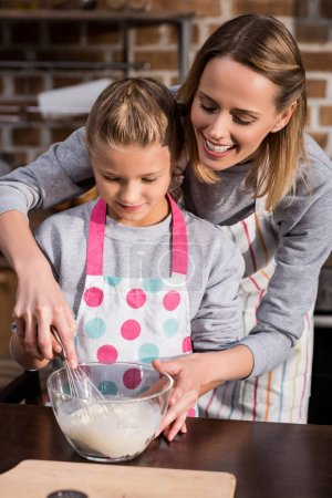 Photo for Mother helping little daughter while making cookies together at home - Royalty Free Image