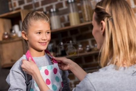 mother putting on apron on daughter
