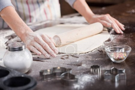 woman rolling raw dough