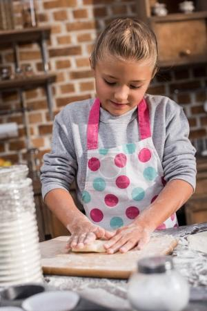 Photo for Portrait of focused little girl rolling raw dough while cooking at home - Royalty Free Image
