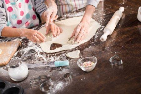 Photo pour Vue partielle de la famille découpe les biscuits sur la pâte crue ensemble - image libre de droit