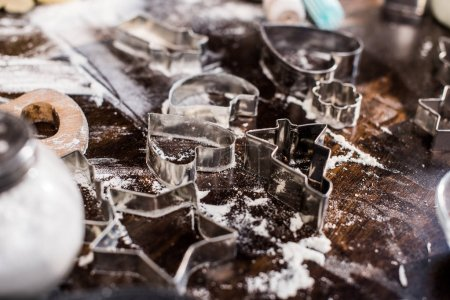 Photo for Selective focus of various cookie cutters and flour on tabletop - Royalty Free Image
