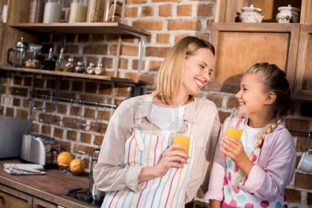 Photo pour Mère et fille souriantes dans des tabliers tenant des verres de jus dans les mains à la maison - image libre de droit