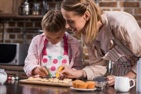 Photo for Portrait of mother and daughter decorating cookies while cooking together at home - Royalty Free Image