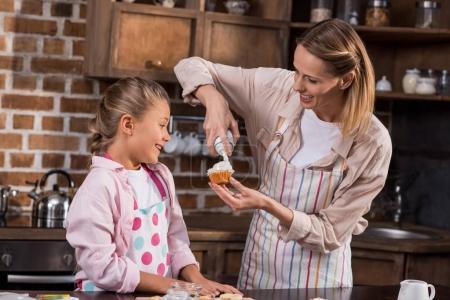 Photo pour Mère et fille en tabliers faire cupcake ensemble à la maison - image libre de droit