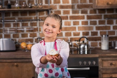 Photo for Portrait of smiling girl in apron showing cupcake in hands and looking at camera - Royalty Free Image