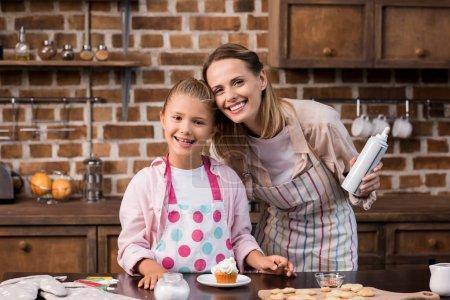 Photo pour Mère et fille en regardant la caméra tout en faisant des cupcake ensemble à la maison de tabliers - image libre de droit