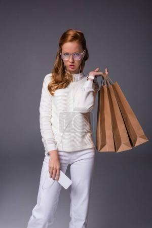 Photo pour Belle fille à la mode de lunettes et des vêtements blancs tenant smartphone et sacs à provisions, isolés sur fond gris - image libre de droit