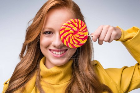 Photo for Beautiful smiling redhead stylish girl holdig lollipop, isolated on grey - Royalty Free Image
