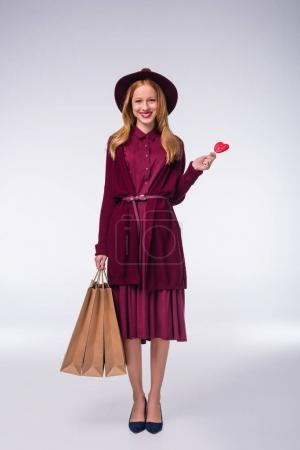 girl with shopping bags and lollipop