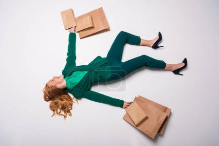 Photo pour Vue du dessus de la fille élégante excitée en costume vert couché avec des sacs à provisions, isolé sur gris, concept shopaholic - image libre de droit