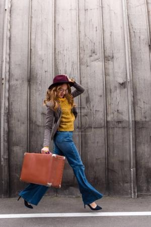 Photo pour Belle fille rousse élégante en chapeau fedora tenant une valise vintage - image libre de droit