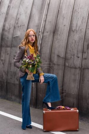 Photo pour Voyageur femelle belle rouquine avec bouquet de fleurs et de la valise vintage - image libre de droit