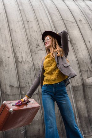 Photo pour Attrayant élégant rousse fille en fedora chapeau tenant valise vintage - image libre de droit