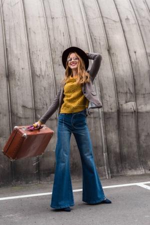 Photo pour Élégante fille rousse élégante en chapeau fedora tenant une valise vintage - image libre de droit