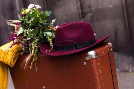 Photo pour Gros plan de valise vintage avec bouquet de fleurs, chapeau fedora et écharpe - image libre de droit
