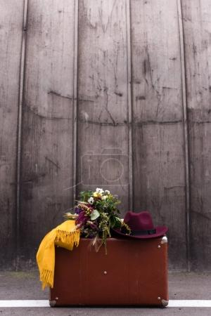 Photo for Vintage suitcase with bouquet of flowers, fedora hat and scarf - Royalty Free Image