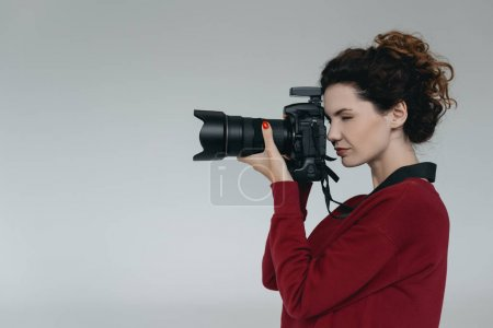 Photo for Professional female photographer with digital photo camera in photo studio, isolated on grey - Royalty Free Image