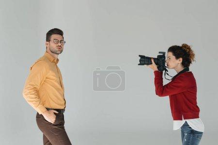 Photo pour Photographe professionnel féminin et beau modèle élégant en studio photo, isolé sur gris - image libre de droit