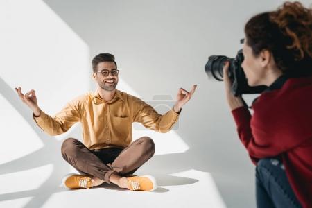 Photo pour Photographe professionnelle et beau modèle en position de lotus en studio photo - image libre de droit