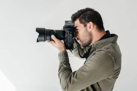 Photo for Professional male photographer with digital photo camera in photo studio, isolated on grey - Royalty Free Image