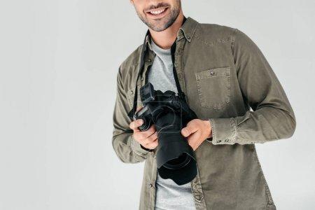 Photo pour Vue recadrée du photographe professionnel masculin avec appareil photo numérique en studio photo, isolé sur gris - image libre de droit