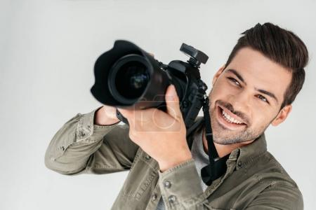 Smiling photographer with digital camera