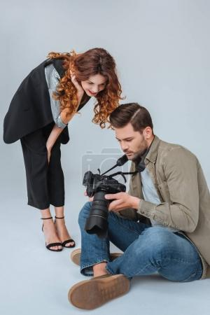 Photo for Attractive model and professional photographer with photo camera on fashion shoot in photo studio - Royalty Free Image