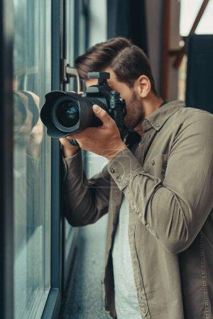 Photo pour Photographe professionnel de sexe masculin avec appareil photo numérique à la fenêtre - image libre de droit