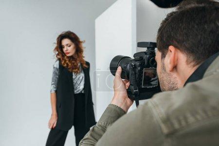 Photo pour Photographe professionnel et beau modèle sur le tournage de mode en studio photo avec équipement d'éclairage - image libre de droit