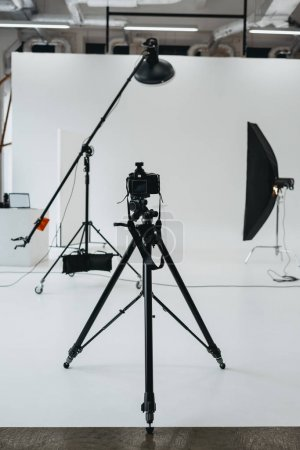 Camera in photo studio with lighting equipment