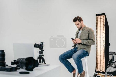 Foto de Fotógrafo profesional masculino con smartphone y cámara de fotos digital en trípode en estudio fotográfico - Imagen libre de derechos